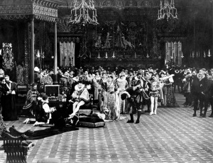 The French Court. The Protestant L'amiral de Coligny (played by Joseph Henabery), bowing, receives a favor from a rather truculent Henry II (described as Henry III in the film and played by Maxfield Stanley) thereby inflaming the Catholic intolerance of Catherine de Médici (played by Josephine Crowell). As a result, the St. Bartholomew's Day Massacre. Perhaps the intolerance of the KKK to Catholics is a result of this event? (Click to enlarge.)