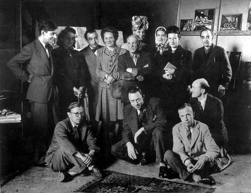 Photograph taken by  Brassaï after a performance of Picasso's play El deseo pillado por la cola. Standing from,left to right: Jacques Lacan, Cecile Eluard, Pierre Reverdy, Luoise Leiris, Pablo Picasso, Zanie de Campan, Valentine Hugo, Simone de Beauvoir, Brassaï. Sitting from left to right: Jean-Paul Sartre, Albert Camus, Michel Leiris, Jean Aubier.