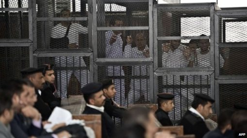 This is how a modern state ought to treat journalists. The Al-Jezeera and BBC journalists (in the cage) on trial in Cairo (Photo: AFP).