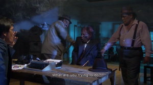 In an interrogation scene out of a Hollywood gangster movie, Koto (l) confronts