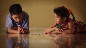 Adi's children play with the larvae of butterflies, a metaphor with significance.