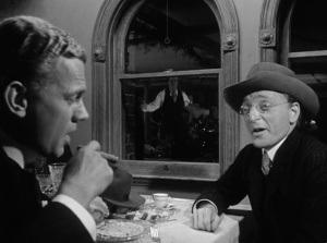 9. Leland and Bernstein discuss the nature of selling out, while a dancing Kane is reflected in the window between them.